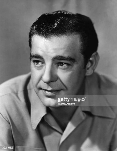 Studio headshot portrait of American character actor Lon Chaney Jr wearing a casual shirt