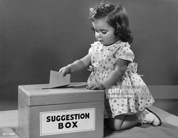 Studio image of a female infant kneeling beside a suggestion box dropping a piece of paper in the slot She wears a dress and white shoes