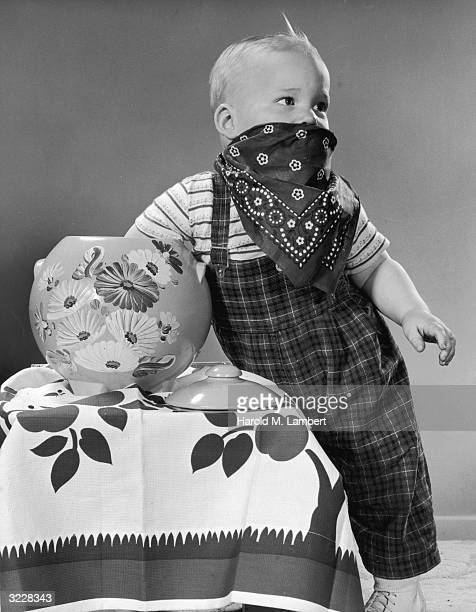 Studio image of a young boy reaching into a cookie jar while posing as a masked bandit with a bandana over his mouth