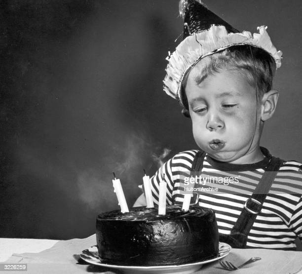 Studio image of a young boy wearing a party hat blowing out the four candles on a chocolate birthday cake