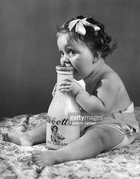Studio image of an infant biting an Abbott's Ice Cream milk bottle which sits between her legs She wears a ribbon in her hair and a cloth diaper