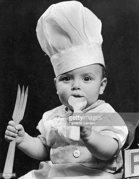 Studio portrait of a baby wearing a chef's hat putting a wooden spoon in his mouth He also holds a large wooden fork