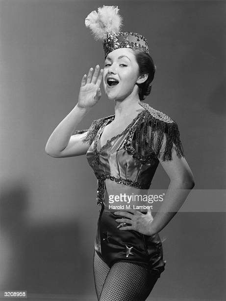 Studio portrait of a woman in a sequined costume with shoulder tassels and a feathered cap holding her hand to her mouth while singing