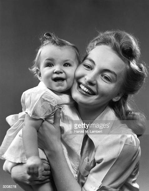 Studio portrait of a woman smiling while holding a baby up to her cheek