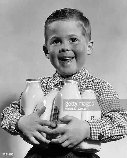Studio portrait of a young boy smiling as he holds four glass bottles of milk in his arms
