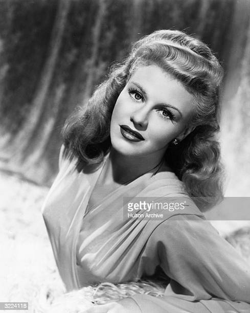 Studio portrait of American actor and dancer Ginger Rogers wearing an evening gown and leaning one arm on a cushion