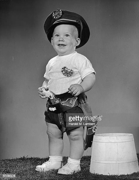 Studio portrait of an infant boy smiling and wearing a police hat a 'CHIEF' badge a holster and a toy pistol in his belt