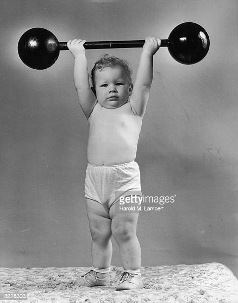Studio portrait of an infant standing and holding a toy barbell over his head in a cloth diaper