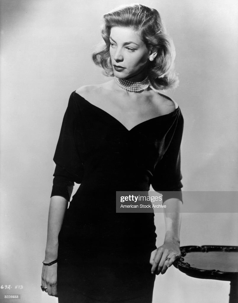 Studio promotional portrait of American actor Lauren Bacall wearing a pearl choker and low cut evening dress standing and looking to the side leaning...
