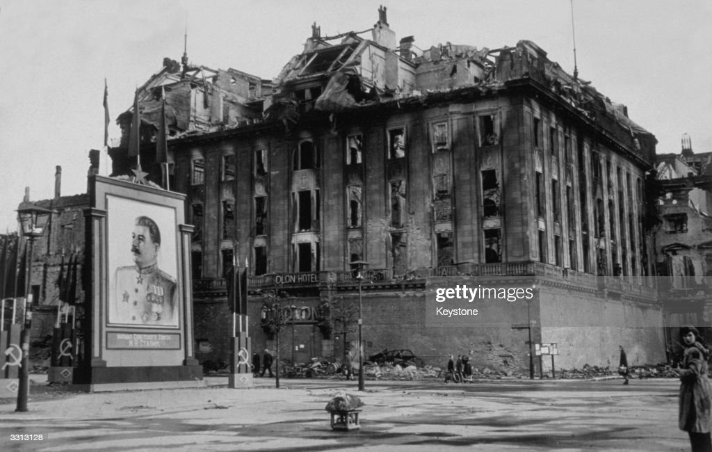 The damaged Adlon Hotel on the Unter Den Linden in Berlin next to a vast picture of Stalin erected by the Russians