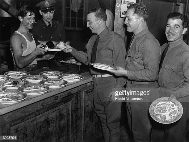 Three soldiers smile while standing on line for a meal at a US military mess hall World War II