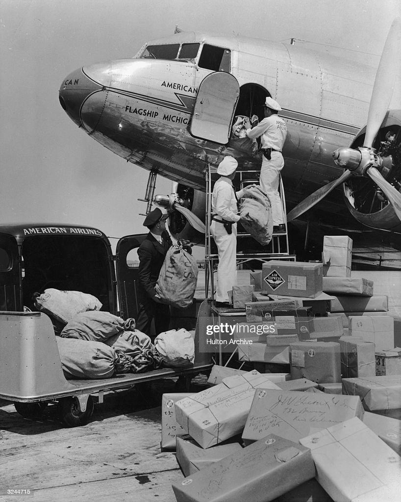 Three uniformed airline workers load air express packages from the back of a truck into an airplane for shipment.