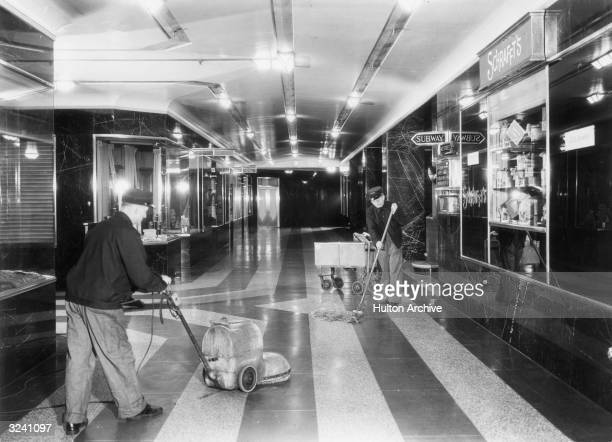 Two male janitors use a floor mop and buffer to clean the surface of the floor of a corridor inside the Grand Central Station terminal New York City...