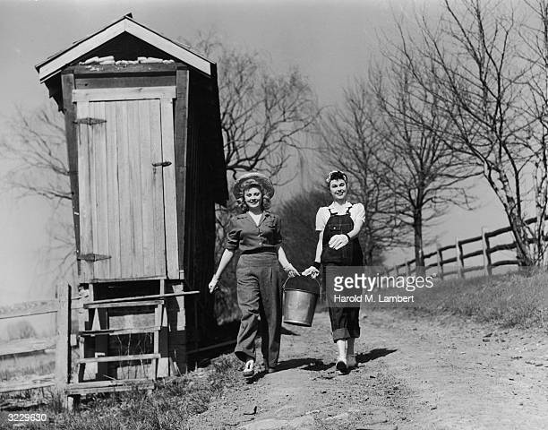 Two young women smile as they walk down a rural dirt road carrying a metal pail past an outhouse One wears a blouse and trousers while the other...