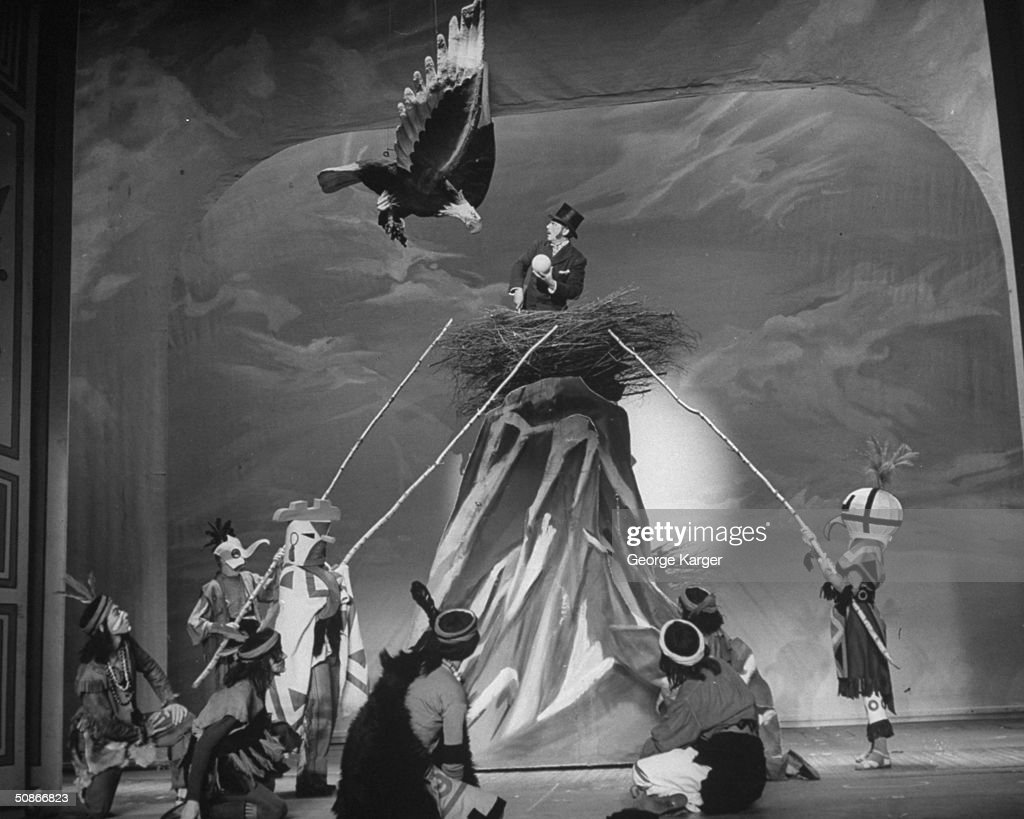 A man trying to steal an Eagle's egg in the play 'Around the World.'
