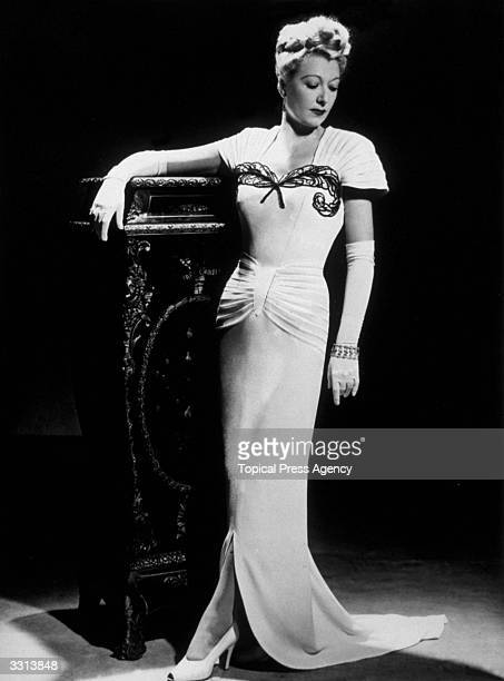 A model wearing a white evening gown designed by Arthur Banks