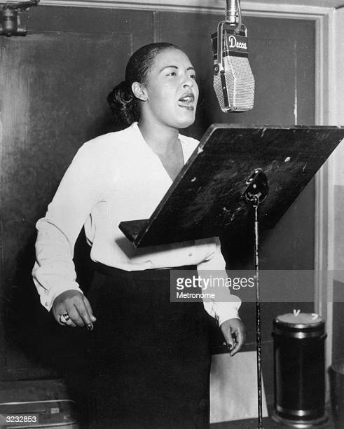 EXCLUSIVE American jazz singer Billie Holiday singing into a microphone at a Decca recording session