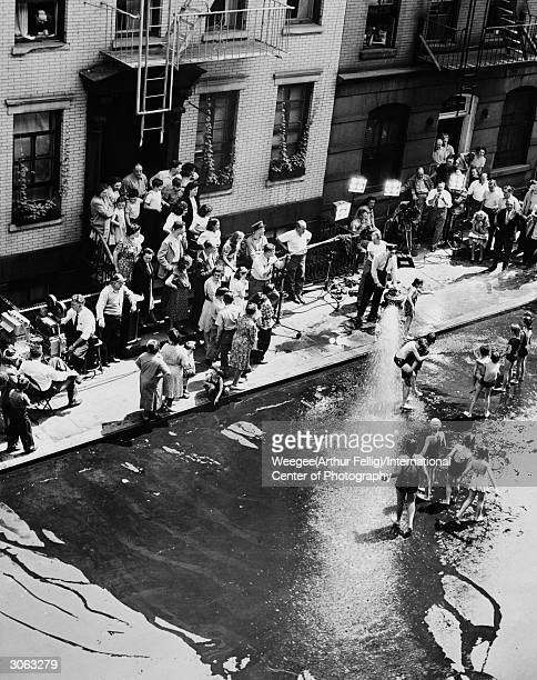A camera crew filming a group of children playing in the spray from a fire hydrant in a New York Street Possibly they are filming a scene for the...