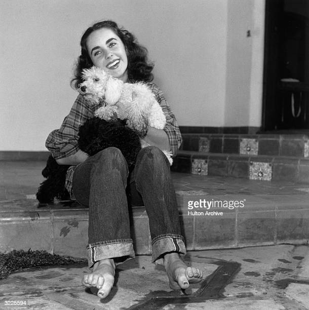 Britishborn actor Elizabeth Taylor wearing a plaid shirt and jeans rolled up at the cuff with bare feet holding a poodle and smiling