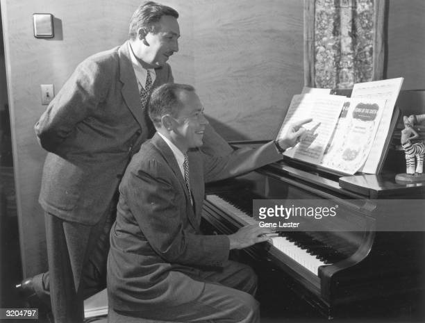 EXCLUSIVE American animator and producer Walt Disney and singer/songwriter Johnny Mercer look over sheet music for 'Song of the South' Disney stands...