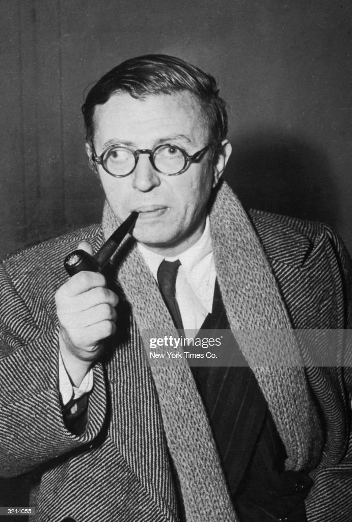 French existentialist author Jean-Paul Sartre (1905 - 1980) smokes a pipe wearing a trenchcoat, scarf and glasses.