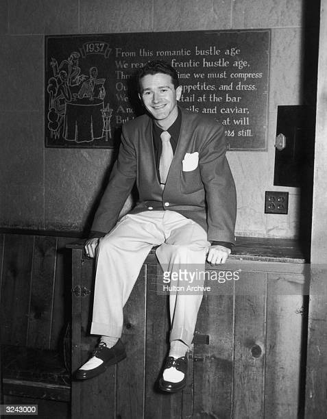 Portrait of American comedian and actor Red Buttons seated on a wooden cabinet near a plaque at Grossinger's Resort Catskills New York