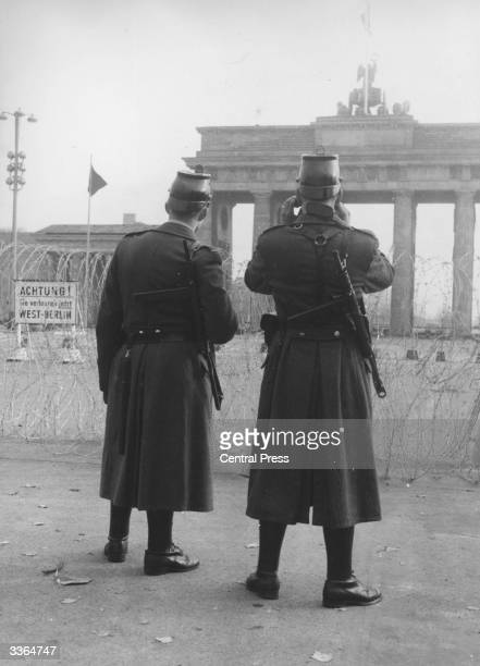 Two armed border guards standing at barbed wire fortifications in East Berlin The Brandenburg Gate is in the background