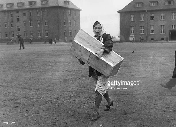 A Russian woman carrying a small coffin containing the body of her dead child across a courtyard at the 2nd Army's Displaced Persons Centre formerly...