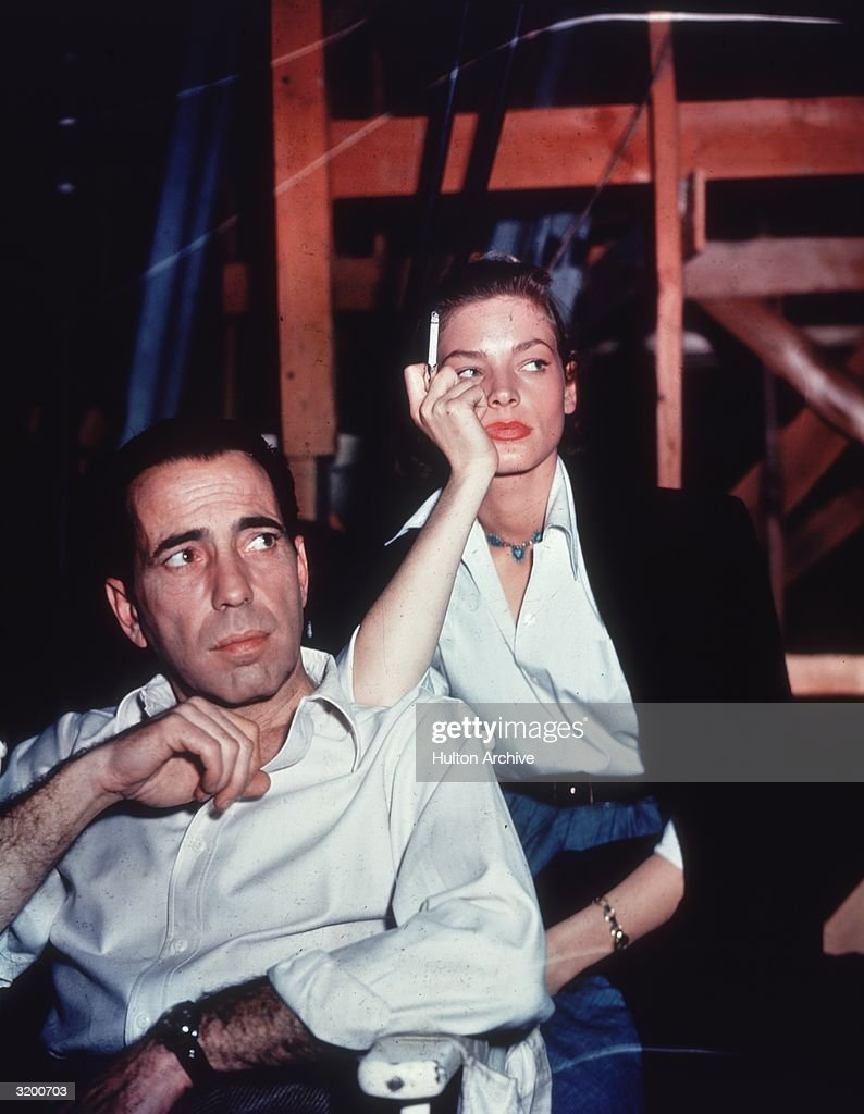 American actor Lauren Bacall smoking a cigarette and leaning on the shoulder of her husband actor Humphrey Bogart on the set of the film 'Key Largo'
