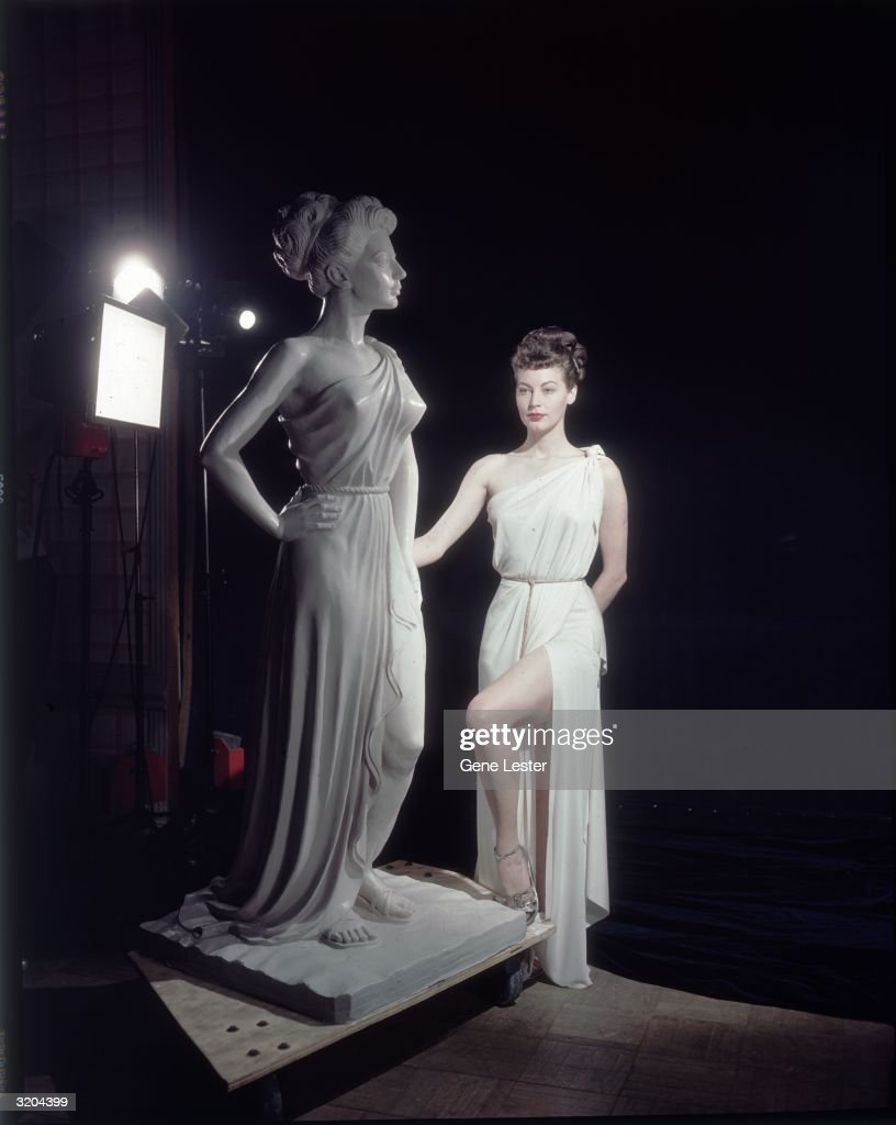 Full-length image of American actor Ava Gardner (1922-1990) posing next to a statue of herself as Venus, the Roman goddess of love, in a promotional portrait for director William A. Seiter's film, 'One Touch of Venus'. Gardner and the statue both wear a diplax tied with a cord.