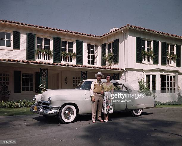 Fulllength image of American actor and country singer Gene Autry posing with his wife Ina Mae Spivey outdoors in front of their white Cadillac at...