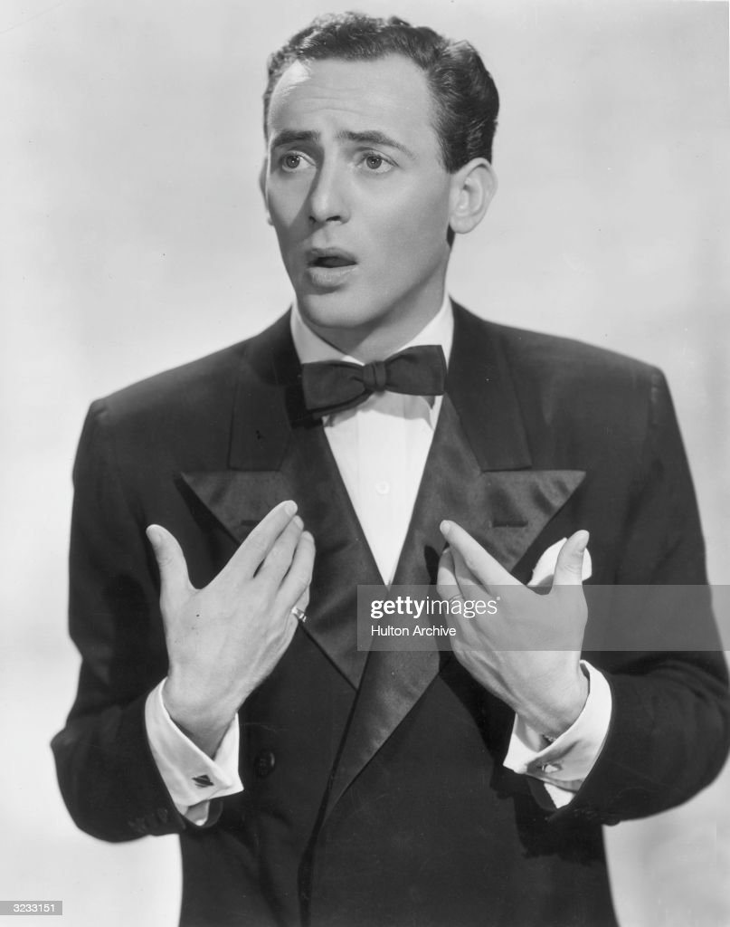 Portrait of American actor and comedian Joey Bishop wearing a tuxedo and gesturing towards himself.