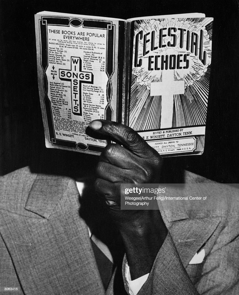 With a song in my heart. A man from Harlem, New York peruses a religious book published by Winsett of Tennessee. (Photo by Weegee(Arthur Fellig)/International Center of Photography/Getty Images)