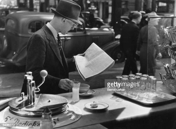 An American catches breakfast at a roadside coffee stall He has a coffee and a fruit juice while reading the paper