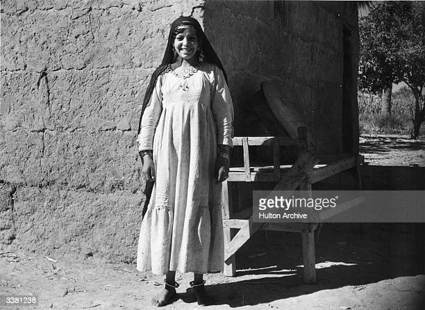 A barefoot Egyptian girl outside her mud built house in Suez