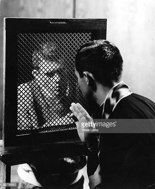 A Catholic priest counselling one of his congregation through the grille of a confessional booth