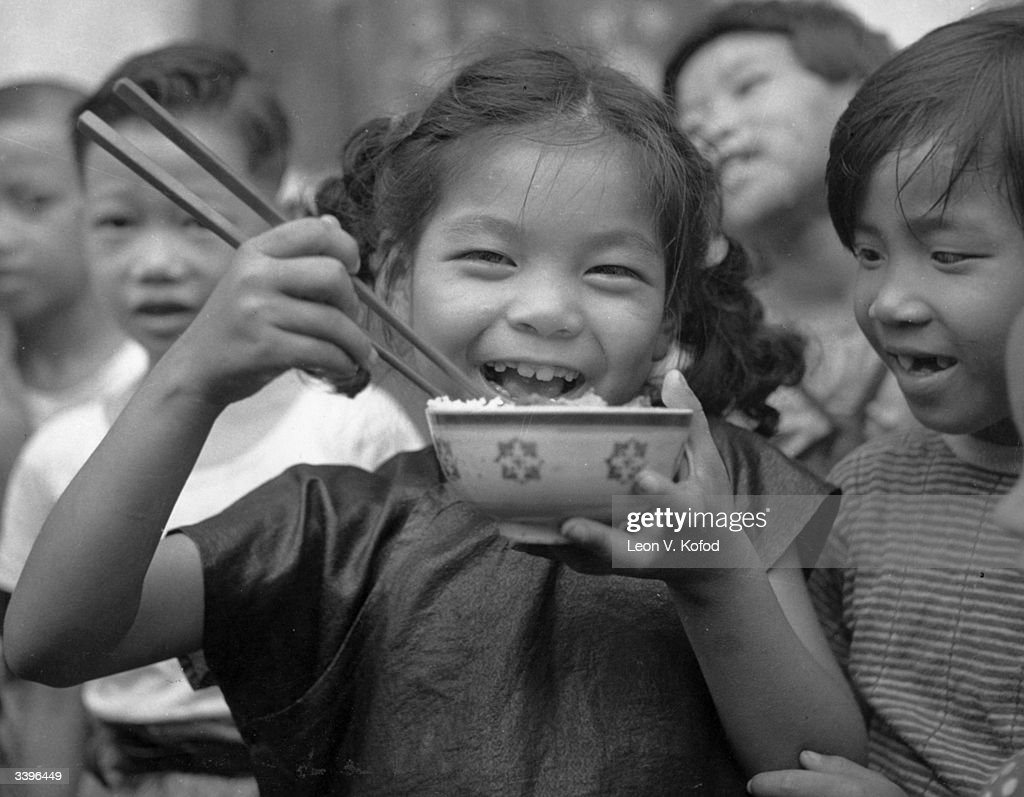 A child smiling whilst she eats a bowl of rice in a Hong Kong refugee camp.