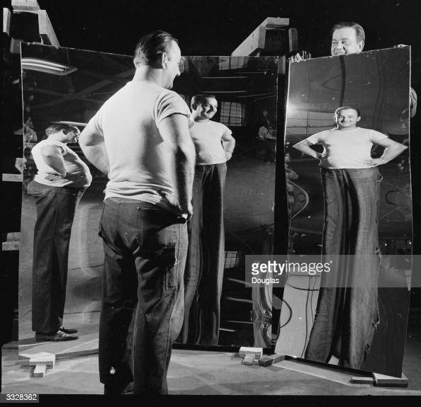 A chubby man sees himself a few stone lighter in a distorting mirror made at the Pittsburgh Plate Glass Co