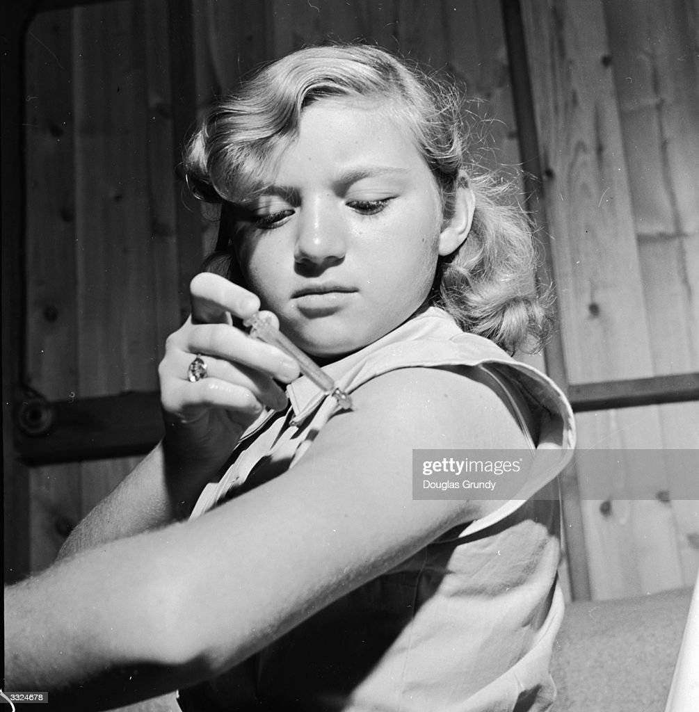 A diabetic girl injecting her arm with insulin