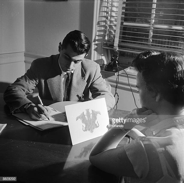 A doctor at the Headache Clinic in the Montefiore Hospital using the Rorschach personality test to determine whether the patient's headaches have a...