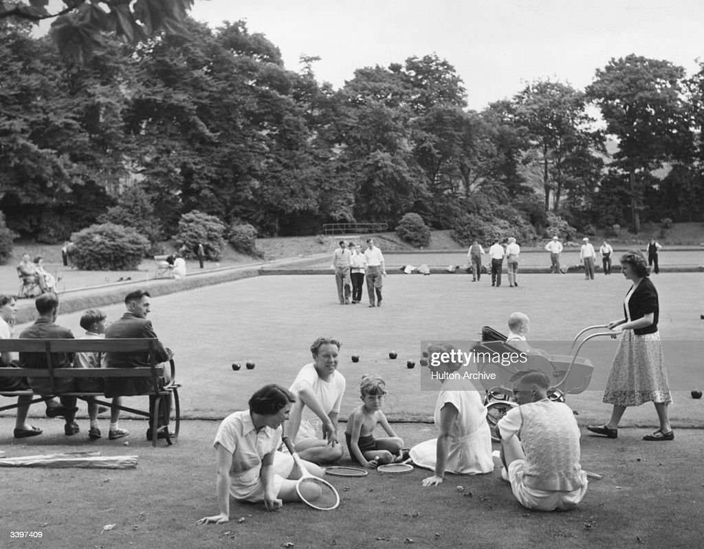 A family relaxing next to a bowling green