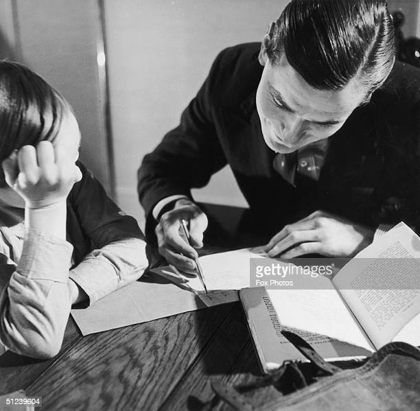 Circa 1950 A father gives his son a little help with his homework