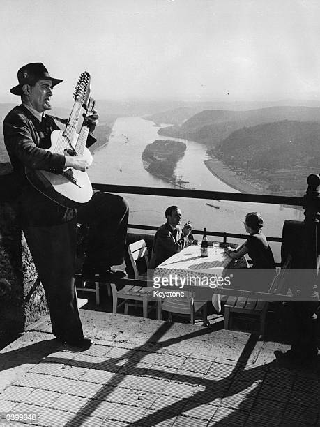 A guitarist serenading diners in a restaurant overlooking a river