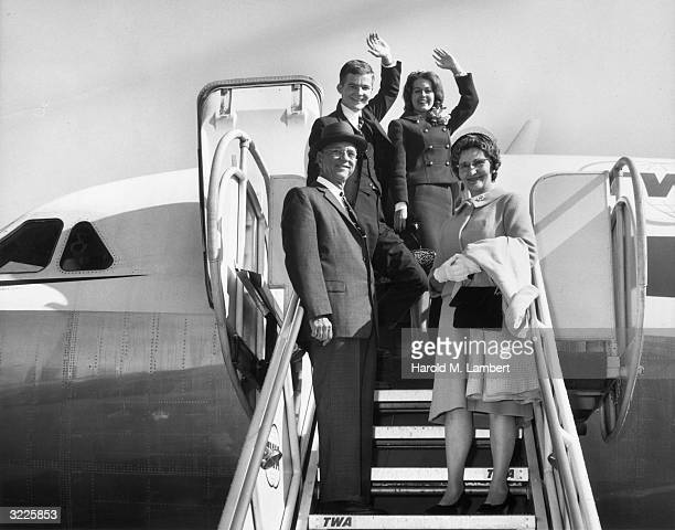 A man and woman wave as they stand on the boarding steps of a TWA airplane with an elderly couple