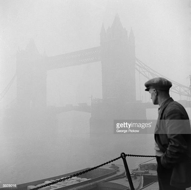 A man peers through the dense London fog at Tower Bridge its bascules closed for traffic to pass over