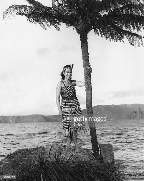 A Maori woman wearing traditional dress stands next to a palm tree on the shore of Lake Rotura New Zealand