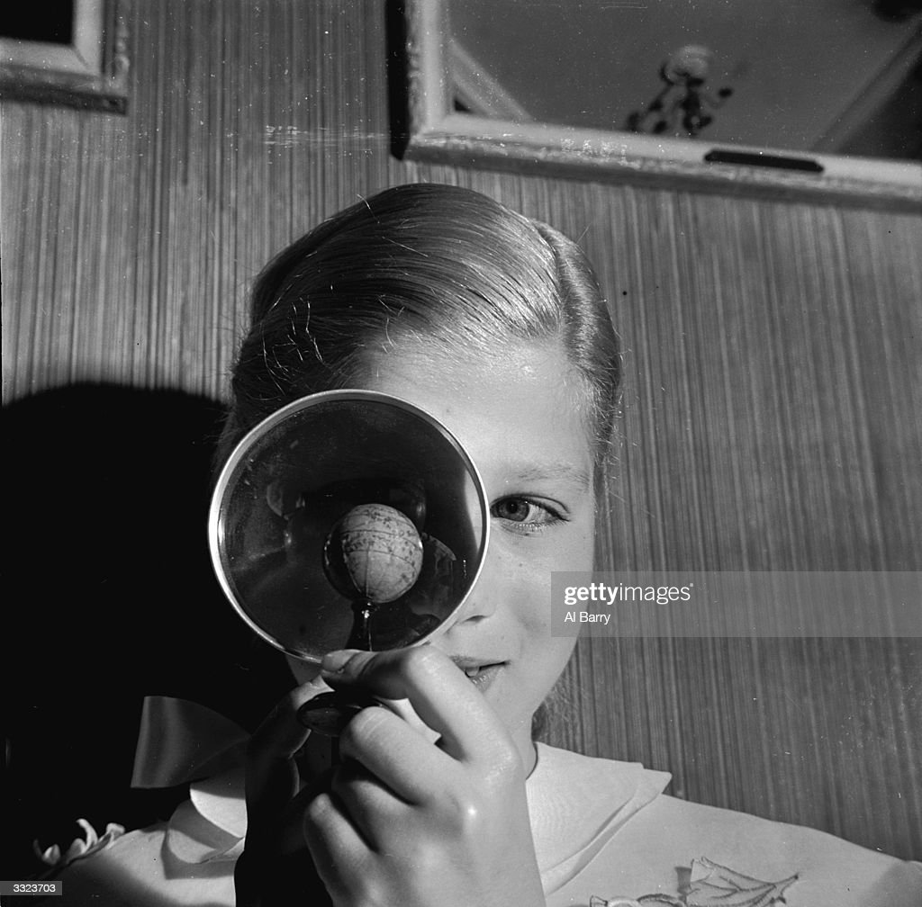 A miniature globe belonging to the Helena Rubinstein collection being examined with the help of a magnifying glass.