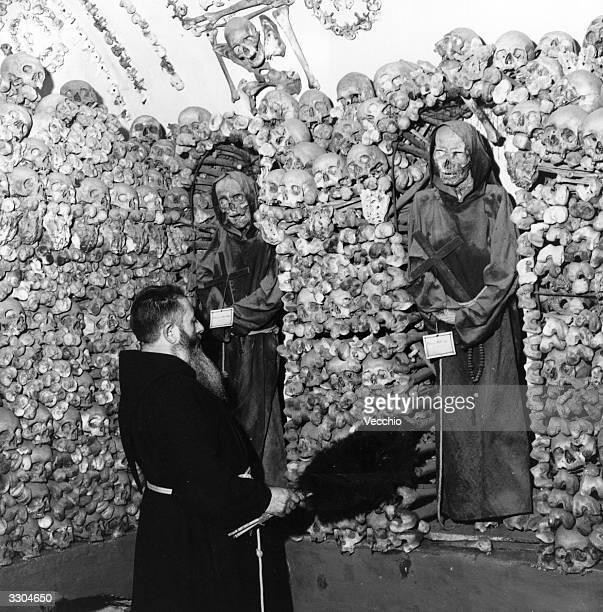 A monk dusts down the remains of his dead comrades in the tombs and the catacombs of a Rome monastery