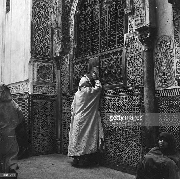 A Moroccan passerby throwing offerings of coins into a hole in the door of the Moulay Idris Mosque in Fez
