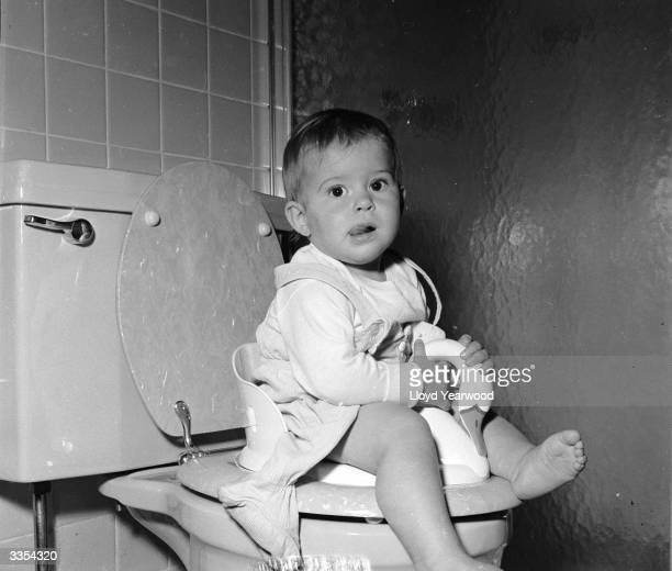 A one year old learns to use the lavatory with her own special toilet seat